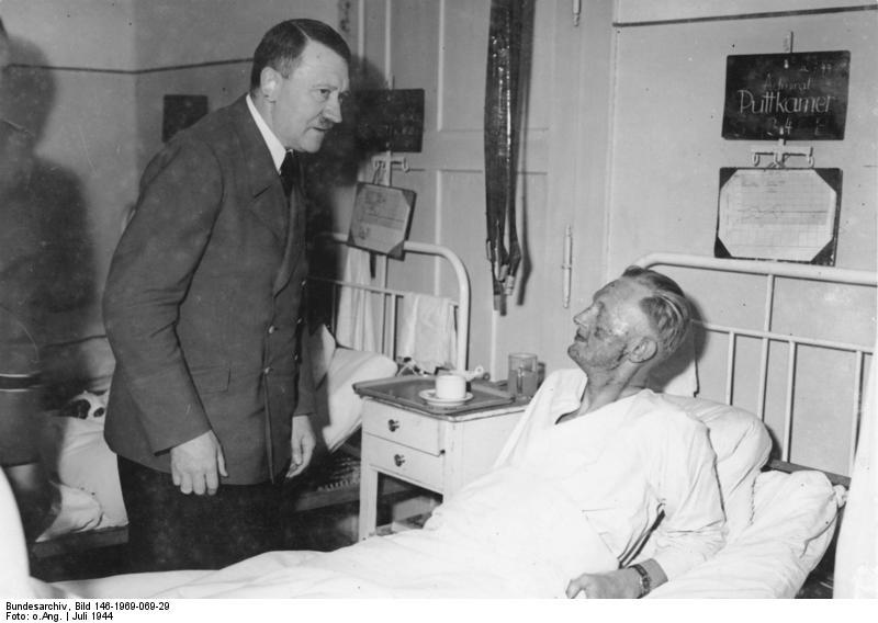 Adolf Hitler (vlevo), Karl-Jesco von Puttkamer (v posteli). Hitler při návštevě raněných při jeho atentátu 22.června 1944.