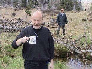 Bedřich Ludvík pije vodu z Luzného potoka a průvodce ing. Bohm váhavě přihlíží.